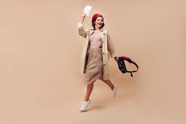 Mulher atraente em uma trincheira elegante e boina vermelha brilhante salta sobre fundo bege e detém ingressos em pano de fundo isolado.