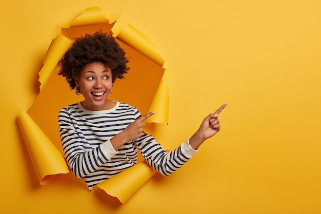Mulher atraente encaracolada com pontos de jumper listrados à parte no espaço em branco