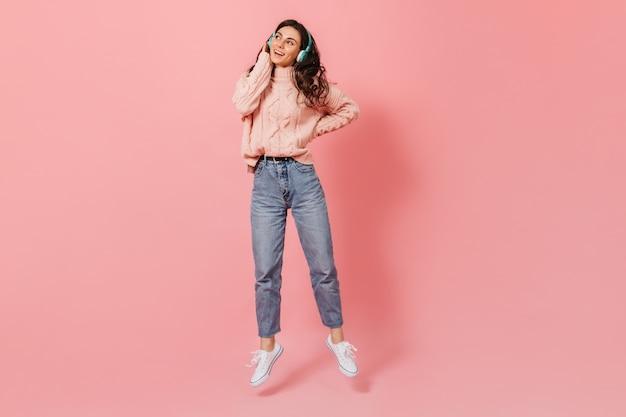 Mulher atraente encaracolada em jeans azuis mães e blusa pulando no fundo rosa, ouvindo música em fones de ouvido.