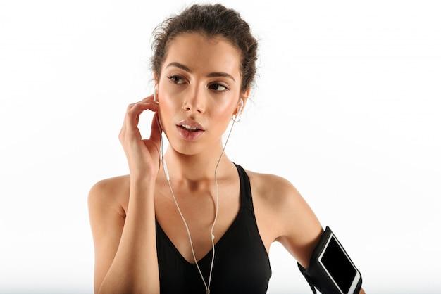 Mulher atraente encaracolado morena fitness relaxante e desviar o olhar
