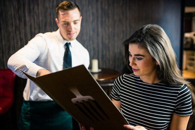 Mulher atraente encomendar ao garçom do menu no restaurante