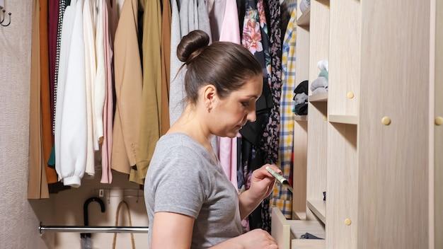 Mulher atraente esconde notas de dólar salvas sob a pilha de roupas em uma gaveta de madeira em um amplo closet em casa.