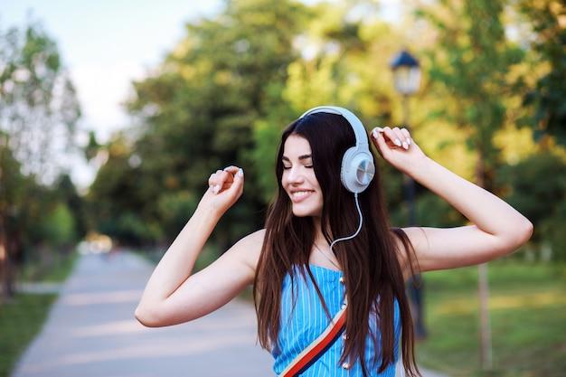 Mulher atraente está dançando enquanto ouve música ao ar livre.