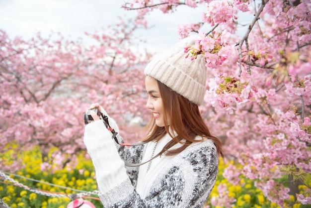 Mulher atraente está desfrutando com flor de cerejeira em matsuda, japão