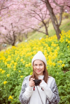 Mulher atraente está sorrindo com flor de cerejeira em matsuda, japão