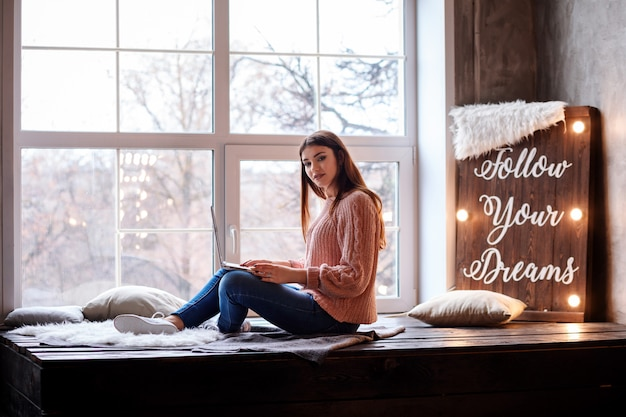 Mulher atraente está trabalhando no bloco de notas enquanto está sentado perto da janela panorâmica. siga seus sonhos rotulando no painel de luzes.