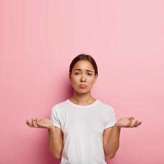 Mulher atraente étnica espalha as palmas das mãos com incerteza, tem olhar infeliz, enfrenta situações difíceis, vestida com roupa casual branca, posa contra a parede rosa. pessoas, dúvida e inconsciência