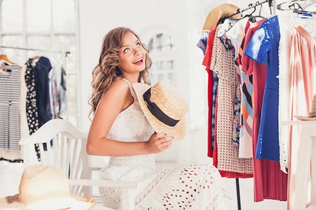Mulher atraente, experimentando um chapéu. feliz compras de verão.