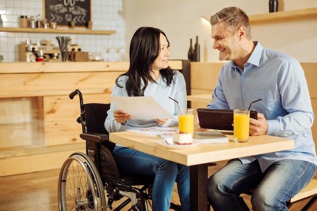 Mulher atraente exuberante com deficiência e um homem loiro feliz e bonito sorrindo e discutindo trabalho enquanto estão sentados em um café