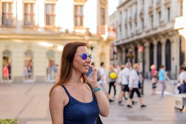 Mulher atraente, falando ao telefone na rua