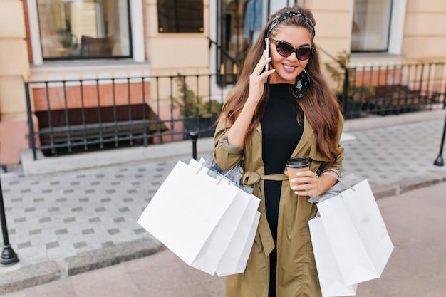 Mulher atraente fashionista de cabelos compridos ligando para alguém durante as compras de fim de semana