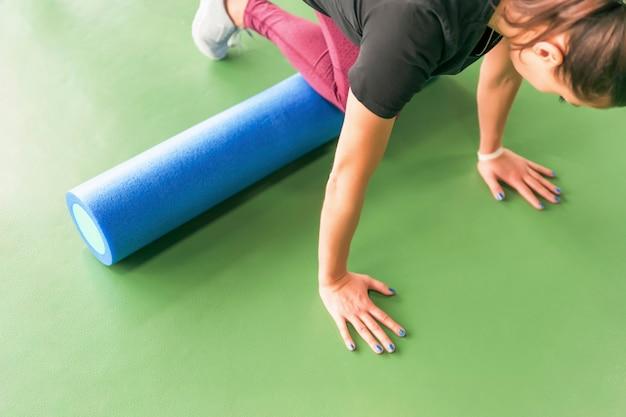 Mulher atraente, fazendo exercícios de rolo de espuma e posando no moderno centro de fitness brilhante