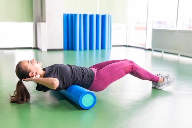 Mulher atraente, fazendo exercícios de rolo de espuma relaxando as costas e posando no moderno centro de fitness brilhante