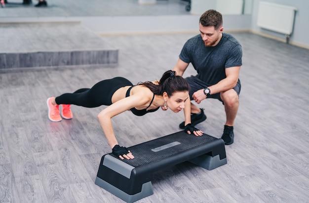 Mulher atraente fazendo flexão com a ajuda de um instrutor pessoal isolado na madeira