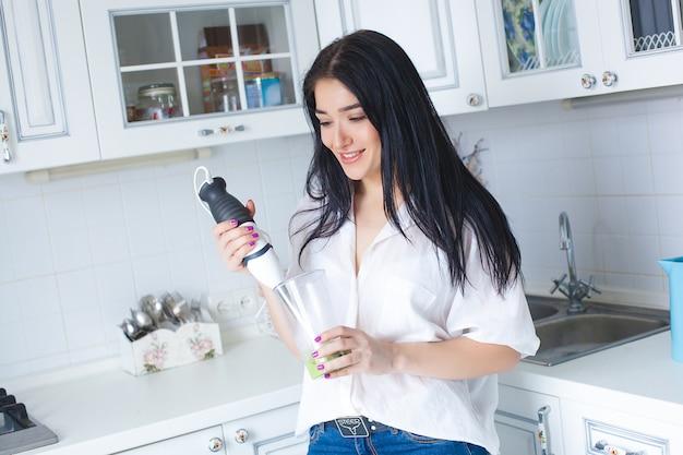 Mulher atraente fazendo smoothie dentro de casa