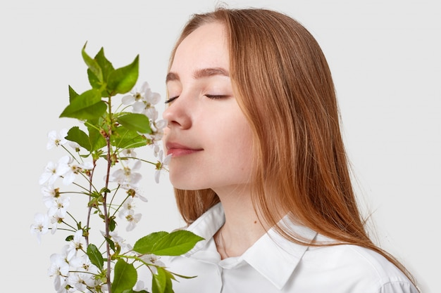Mulher atraente feliz cheira a flor de cerejeira