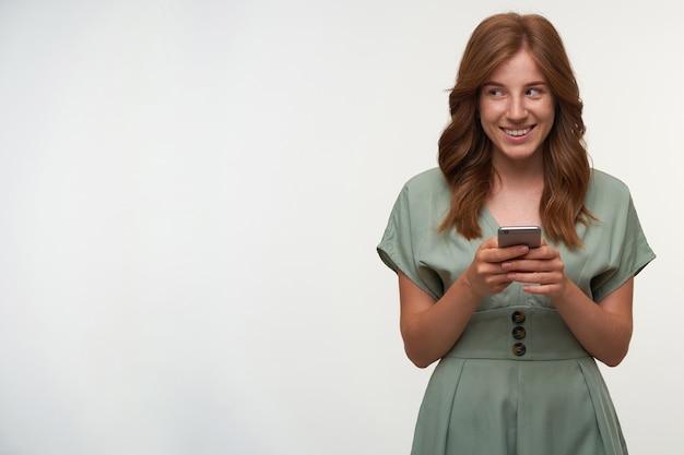 Mulher atraente feliz com cabelo ruivo posando com o celular nas mãos, olhando para o lado e sorrindo feliz, usando um vestido romântico