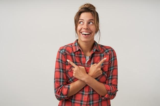 Mulher atraente feliz com penteado de coque olhando para cima, cruzando as mãos no peito e apontando com os indicadores para lados diferentes e sorrindo amplamente