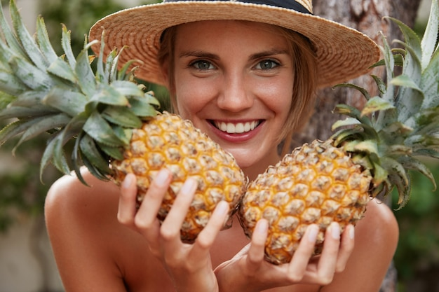 Mulher atraente feliz com sorriso largo segurando dois abacaxis