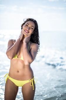 Mulher atraente feliz de biquíni em pé na beira-mar