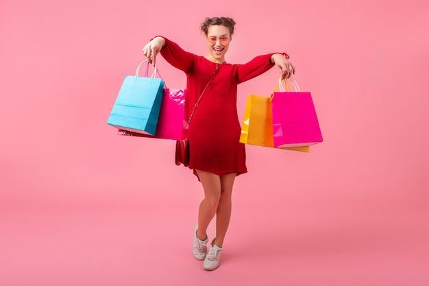 Mulher atraente, feliz e elegante, shopaholic em um vestido vermelho da moda segurando sacolas coloridas na parede rosa isolada, venda animada, tendência da moda primavera-verão