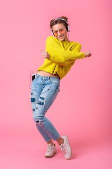 Mulher atraente feliz e engraçada dançando ouvindo música em fones de ouvido, vestida com roupa de estilo colorido moderno, isolada no fundo rosa do estúdio
