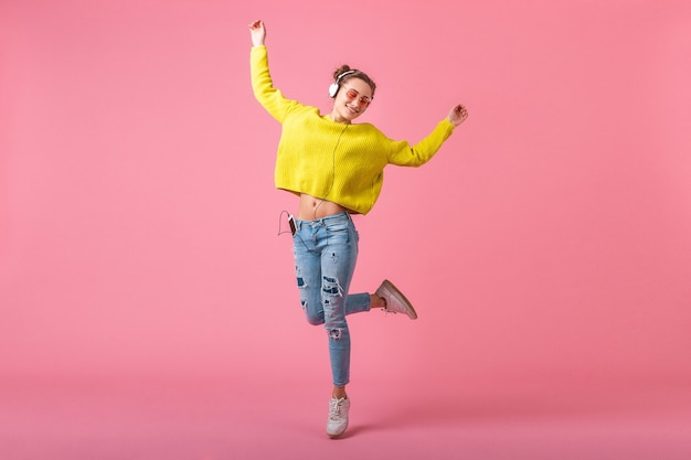 Mulher atraente feliz e engraçada em um suéter amarelo pulando ouvindo música em fones de ouvido, vestida com uma roupa de estilo moderno colorido isolada na parede rosa, se divertindo