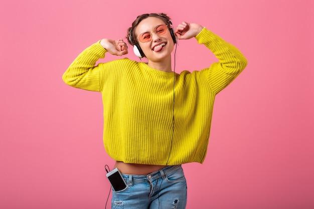 Mulher atraente feliz e engraçada ouvindo música em fones de ouvido, vestida com roupa de estilo colorido moderno, isolada na parede rosa, vestindo suéter amarelo e óculos escuros, se divertindo