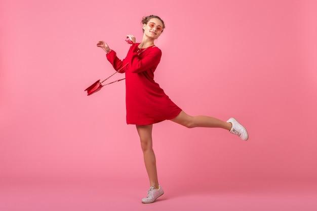 Mulher atraente, feliz e sorridente elegante em um vestido vermelho da moda, pulando correndo na parede rosa isolada, tendência da moda primavera-verão, humor romântico garota glamour