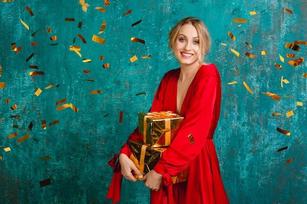 Mulher atraente feliz e sorridente em um elegante vestido vermelho comemorando o natal e o ano novo com presentes