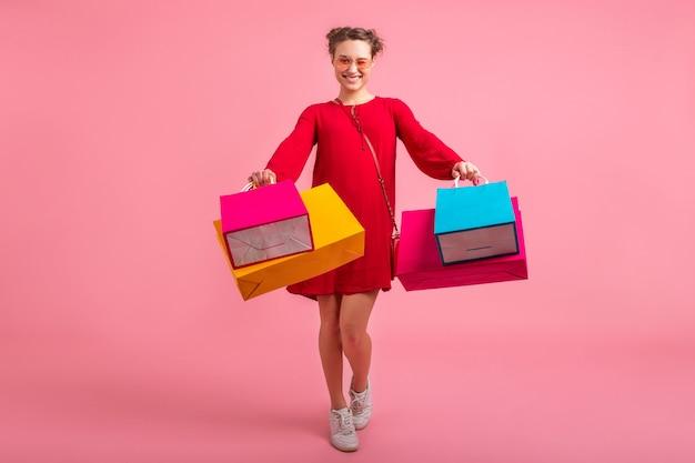 Mulher atraente feliz e sorridente por shopaholic em um vestido vermelho da moda segurando sacolas coloridas na parede rosa isolada, venda animada, tendência da moda