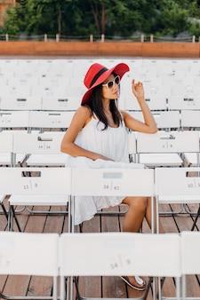 Mulher atraente feliz e sorridente vestida de vestido branco, chapéu vermelho, óculos de sol, sentada no teatro ao ar livre de verão na cadeira sozinha, tendência da moda de primavera