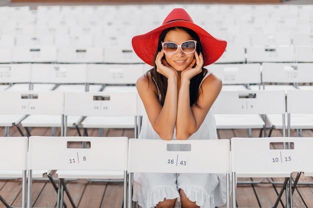 Mulher atraente feliz e sorridente vestida de vestido branco, chapéu vermelho, óculos de sol, sentada no teatro ao ar livre de verão na cadeira sozinha, tendência da moda de primavera Foto gratuita