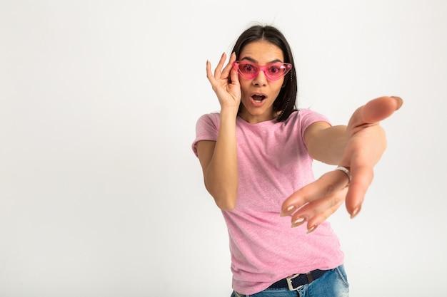 Mulher atraente feliz engraçada emocional em camiseta rosa com braços isolados para a frente