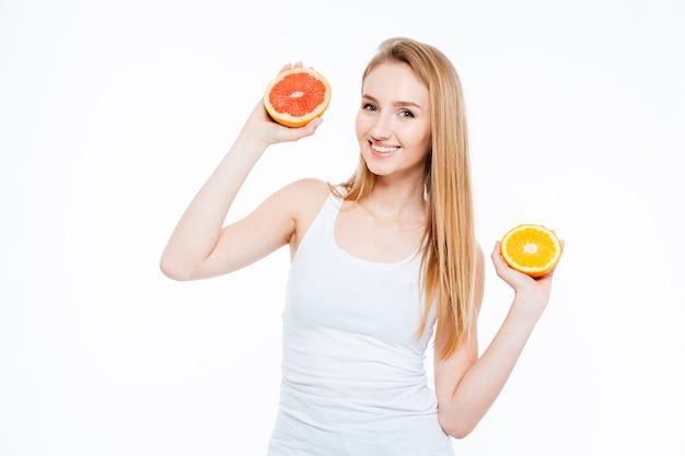 Mulher atraente feliz segurando laranja e toranja isoladas em um fundo branco