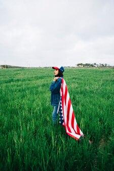 Mulher atraente ficar no campo de verão com bandeira