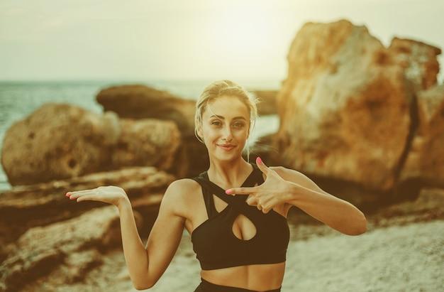 Mulher atraente fitness em roupas esportivas segura a palma da mão para o espaço de cópia e aponta para uma praia selvagem.
