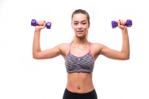 Mulher atraente fitness garota fazendo exercícios aeróbicos diferentes com halteres em branco vestida com roupas esportivas