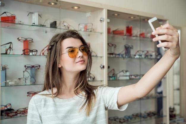 Mulher atraente foi às compras sozinha, fazendo selfie enquanto experimentava novos óculos de sol elegantes na loja de ótica, enviando foto para um amigo