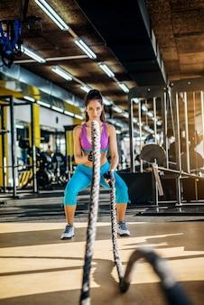 Mulher atraente forte aptidão fazendo exercícios de corda de batalha no moderno ginásio ensolarado.