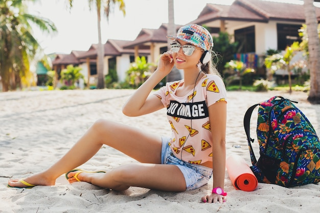 Mulher atraente hippie sentada na praia ouvindo música em fones de ouvido em uma roupa colorida elegante nas férias de verão tropical usando acessórios boné óculos escuros, sorrindo, viajando com uma mochila