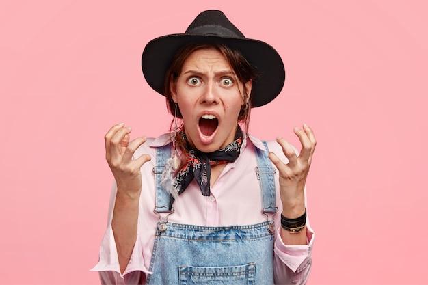 Mulher atraente impaciente gesticula desesperadamente, grita de irritação, fica com raiva de alguém, usa chapéu e macacão jeans, isolada sobre parede rosa