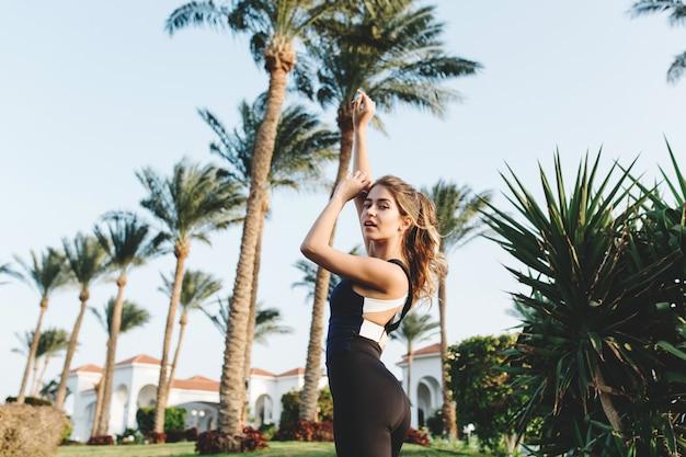 Mulher atraente incrível em roupas esportivas, esticando as mãos acima em palmeiras, céu azul. cidade tropical, procura, trabalho, treino, estilo de vida saudável