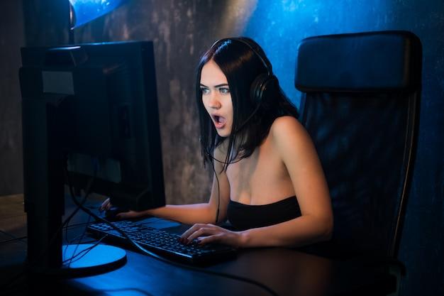 Mulher atraente, jogando videogame em um computador pc, em choque, grita por causa do vírus