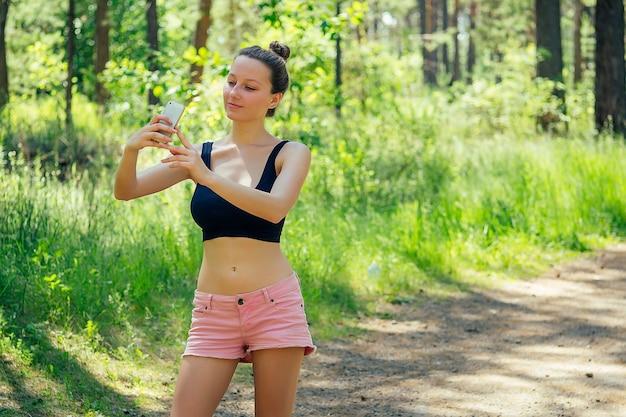 Mulher atraente jovem atlética magro morena sexy corredor em shorts rosa curtos e top preto fazendo selfie telefone r no parque