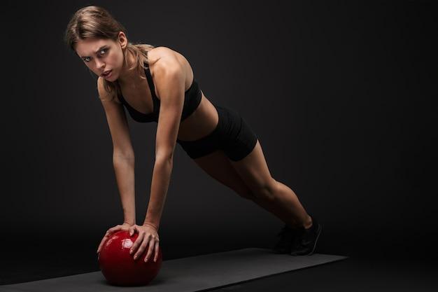 Mulher atraente, jovem e saudável de fitness saudável, usando sutiã esportivo e shorts isolados sobre um fundo preto, fazendo exercícios em uma esteira de fitness, usando medicine ball