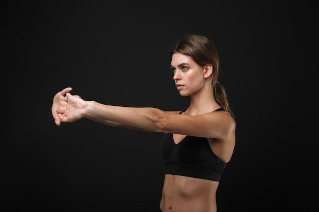 Mulher atraente, jovem e saudável, saudável, usando sutiã esportivo e shorts isolados sobre um fundo preto, fazendo exercícios de alongamento