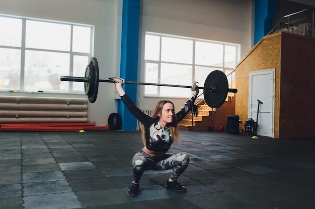 Mulher atraente jovem esportes com barra. deadlift.