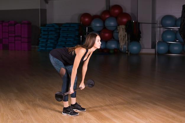 Mulher atraente jovem esportes com peso. deadlift.