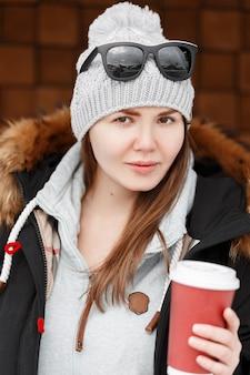 Mulher atraente jovem hippie com uma maquiagem natural com um chapéu de tricô quente de inverno em um moletom com uma jaqueta estilosa de pele segura uma xícara de café na mão